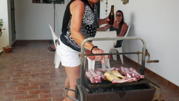šťastná starší dáma vaření na grilu spolu se svou rodinou