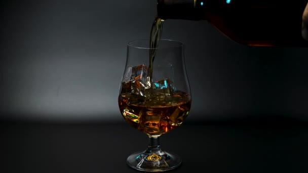 Rövidfilm, amin whiskey-t öntenek egy fekete hátterű tulipánpohárba. Gyönyörű háttér. Az alkohol fogalma.