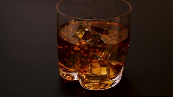 Gyönyörű kilátás közeledik üveg whisky jégkockákkal fekete háttér. Alkohol koncepció. Élelmiszerek és italok.