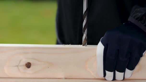 Detailní pohled na muže pracujícího s bezdrátovým šroubovákem na dřevěné desce. Koncept pracovních nástrojů.
