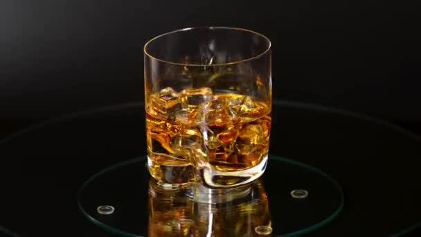 Beautiful view of rotating glass of whiskey with ice cubes. Alcohol and health concept.