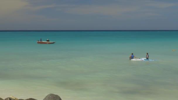 Turisti sulle attività acquatiche nellOceano Atlantico. Esercizio di surf. Superficie dellacqua delloceano turchese che si fonde con il cielo blu. Spiaggia di sabbia bianca e palme verdi. Oranjestad. Aruba. 09.11.2019