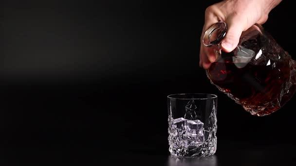 Krátký film s whisky nalitou do sklenice s ledem na černém pozadí. Zpomal. Krásné zázemí. Koncept alkoholu.