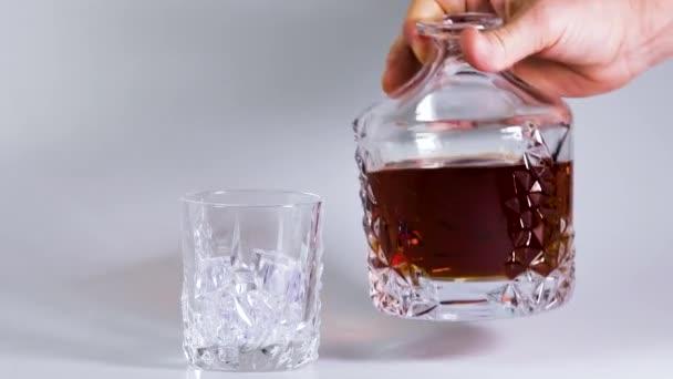 Krátký film s whisky nalitou do sklenice s ledem na bílém pozadí. Krásné zázemí. Alkohol.
