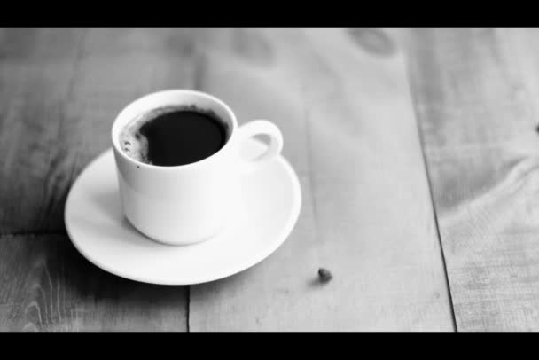 Cup of coffee beside falling coffee beans on wooden board. Black and white colors
