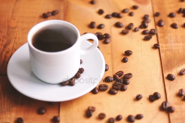 Aroma schwarzer heißer starker Kaffee in weißer Keramiktasse mit Duftdampf neben fallenden Kaffeebohnen auf Holzgrund