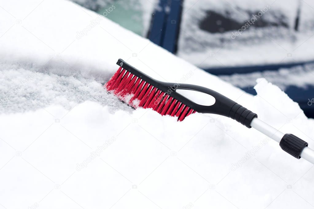 Closeup photo of black brush lying on car covered in snow .