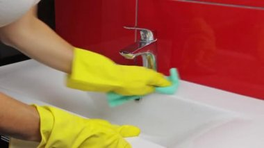 Housewife  in yellow gloves cleans the sink