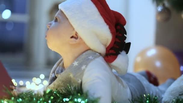 entzückendes Babyspiel neben einem Weihnachtsbaum mit einem Geschenk, lächelt und lacht.