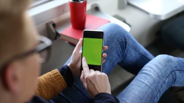 Nő segítségével A mobiltelefon, zöld képernyő chroma-kulcs a vonat Vértes