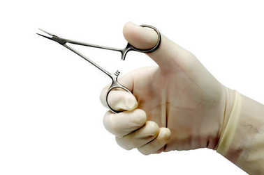 Doctor's hand holding medical artery clamp scissor