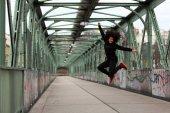 Fotografie Schwarzen Dancehall Tänzer springen auf einer Brücke mit graffiti