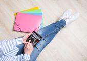 Žena pomocí kalkulačky sedí na podlaze
