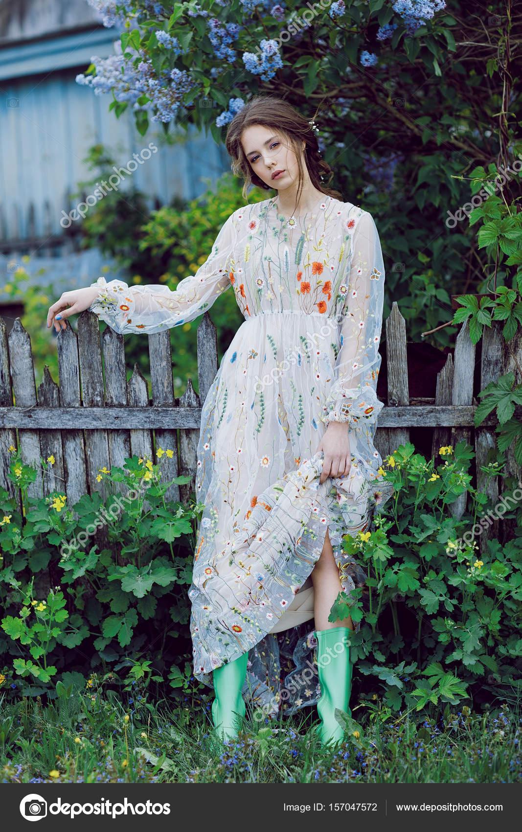Květy kolem dívka v šedé šaty a zelené boty. Portrét mladé atraktivní dívky  v dlouhých šatech letní slunečný den v parku — Fotografie od ... 35b51666c5