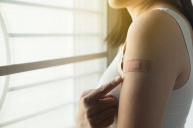 Woman using adhesive bandage plaster on her arm after injection vaccine