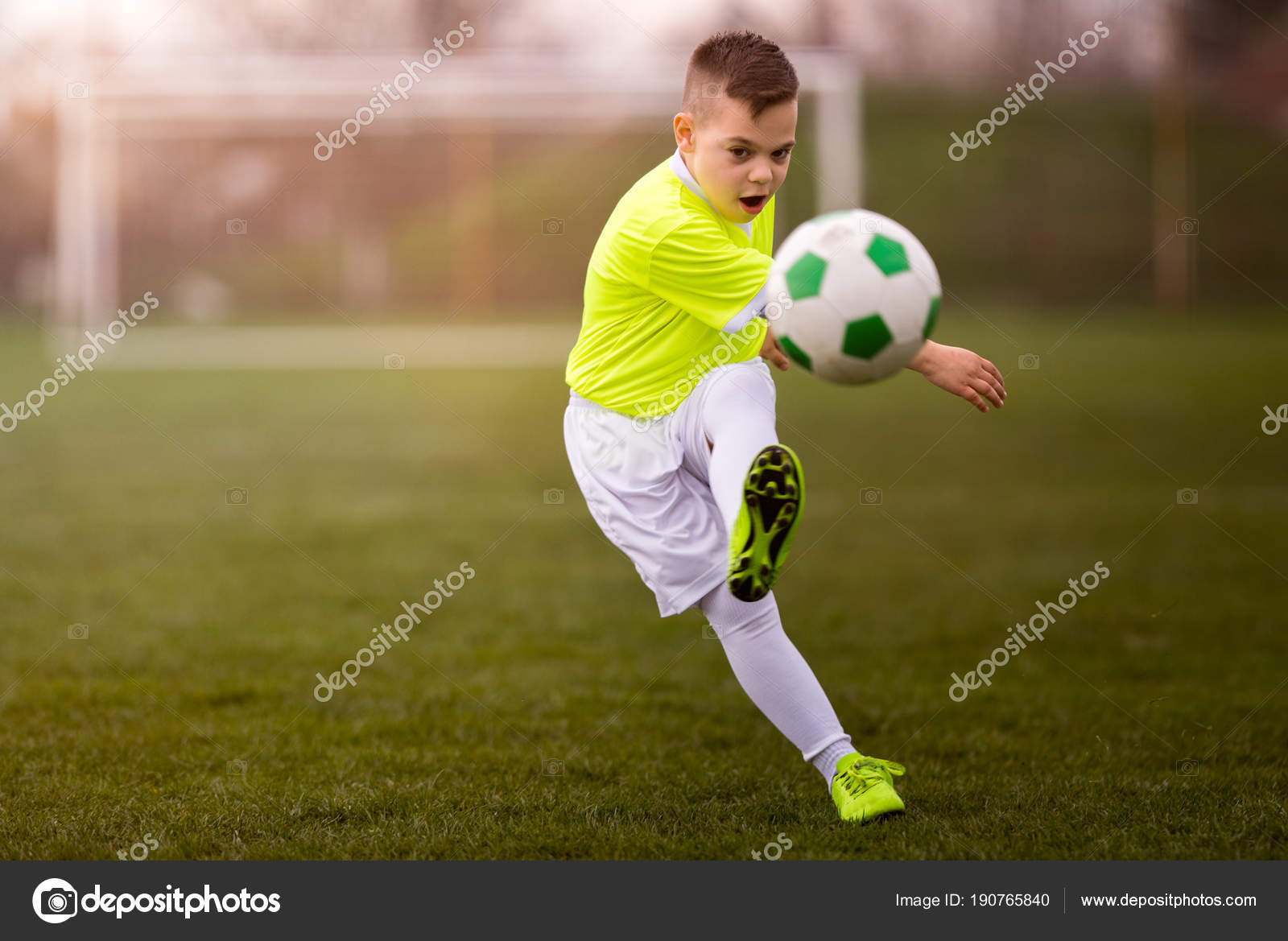 boy kicking football on the sports field stock photo fotokostic