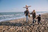 family on seashore in autumn