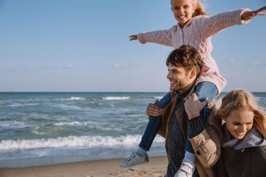 family with happy daughter on seashore
