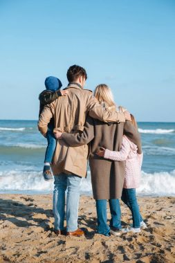 family hugging on seashore