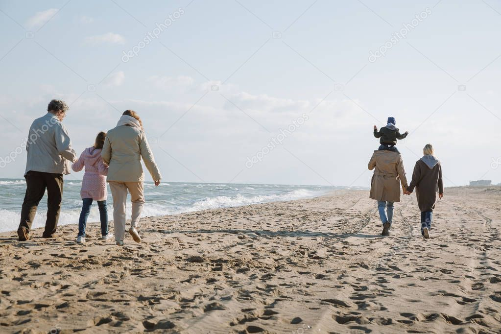 multigenerational family walking on seashore