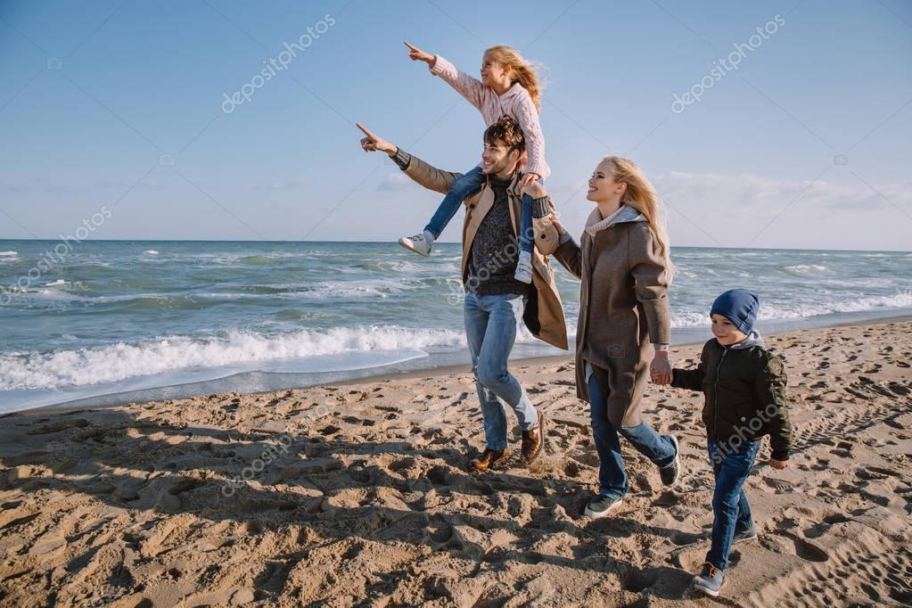 family walking on seashore in autumn