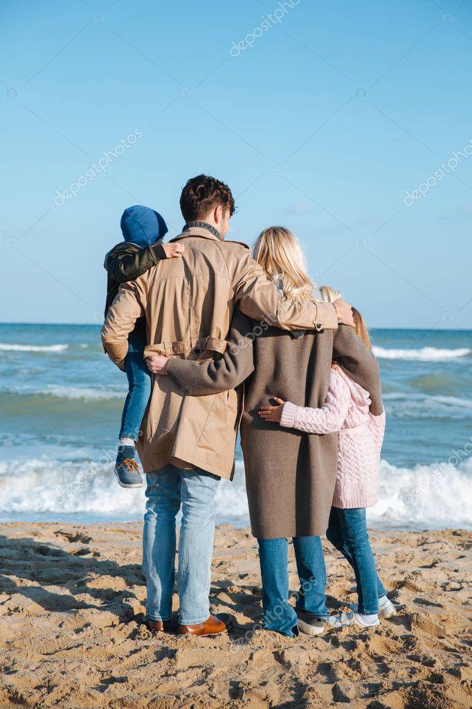 family hugging on seashore