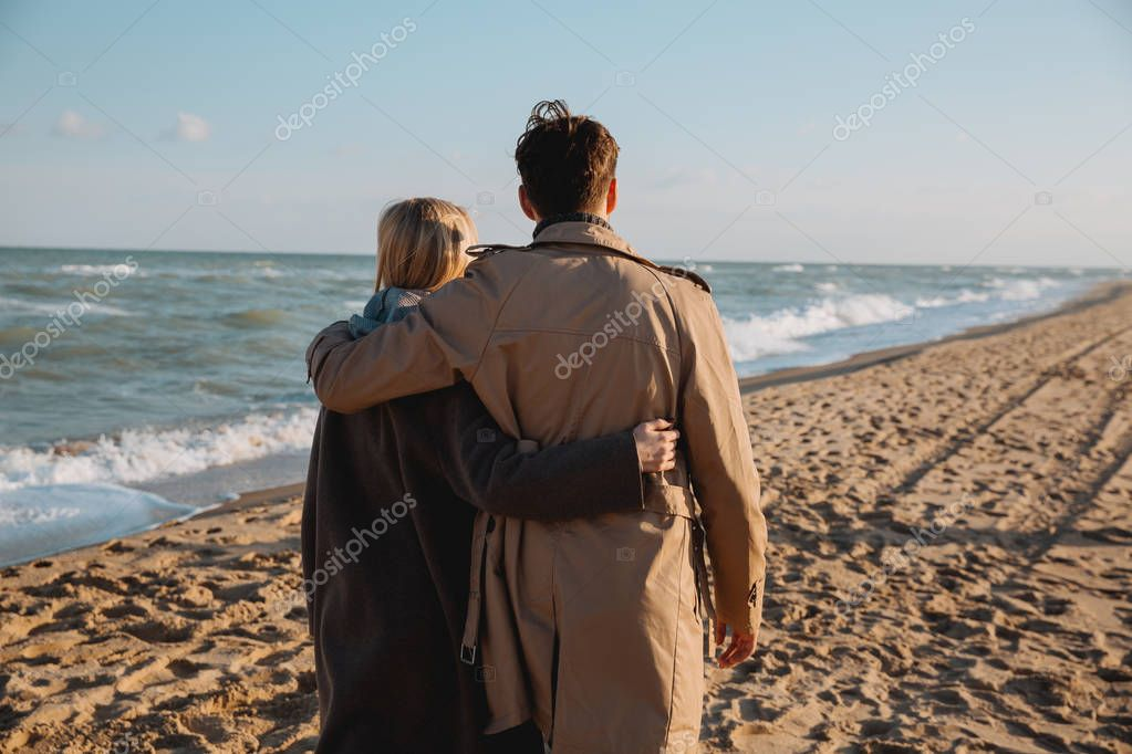 couple embracing and walking on seashore