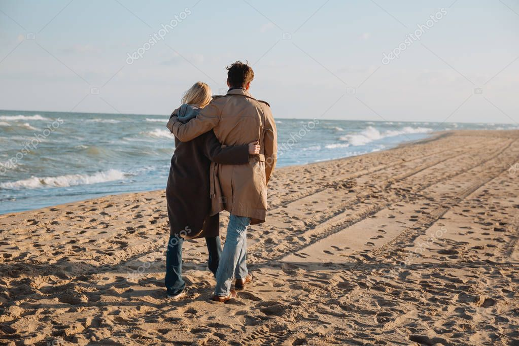 couple hugging and walking at seaside