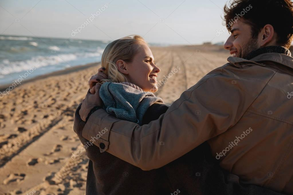smiling couple embracing on seashore