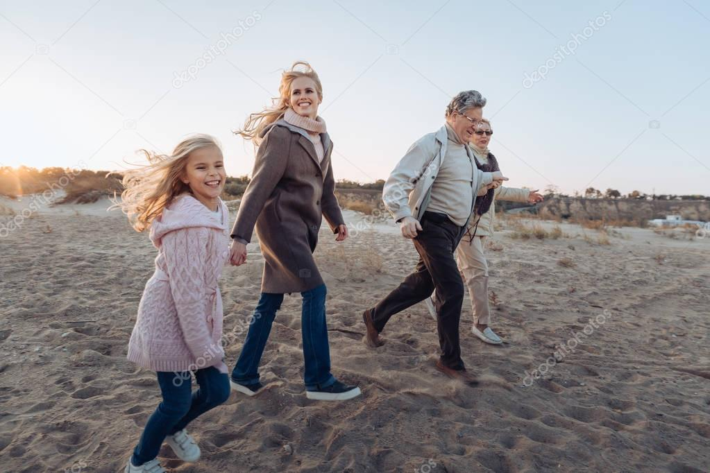 multigenerational family walking on beach