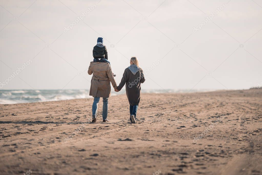 parents and son walking on seashore