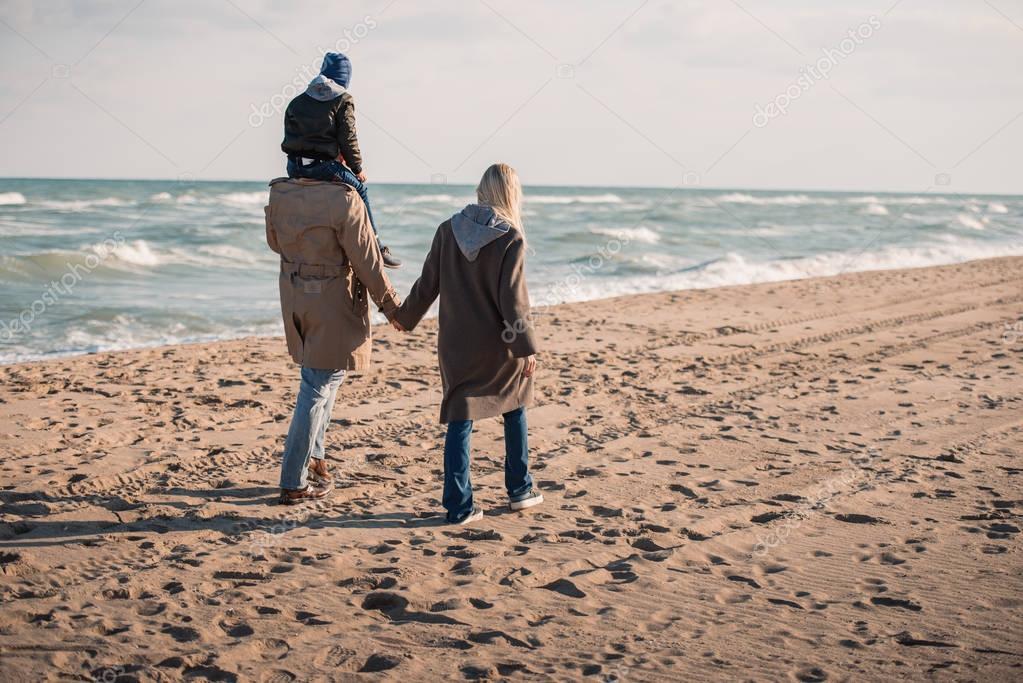 family walking on seashore in autumn
