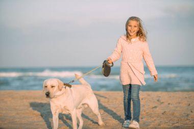 kid walking with dog at seaside