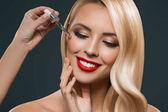 Fényképek gyönyörű szőke lány Pipetta kezelés alkalmazása az arcon, elszigetelt fekete