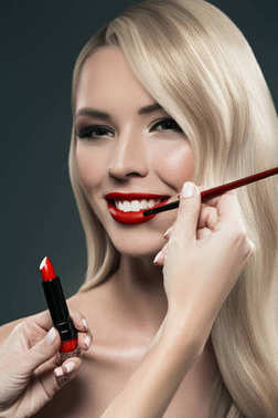 Portrait of beautiful blonde hair girl with visagiste hands applying lipstick with brush, isolated on black