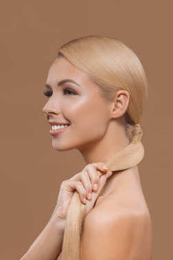 side view of smiling beautiful blonde hair girl isolated on beige