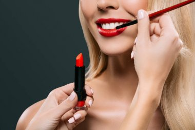Cropped image of beautiful blonde hair girl with visagiste applying lipstick with brush, isolated on black stock vector