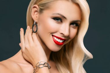 portrait of smiling blonde woman posing in bracelet and earrings, isolated on grey