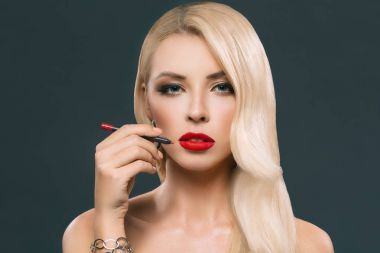 beautiful blonde woman making red lips with cosmetic pencil, isolated on grey