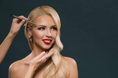 beautiful blonde woman applying eyebrow makeup, isolated on grey