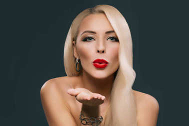 beautiful blonde woman with makeup and hairstyle blowing kiss, isolated on grey