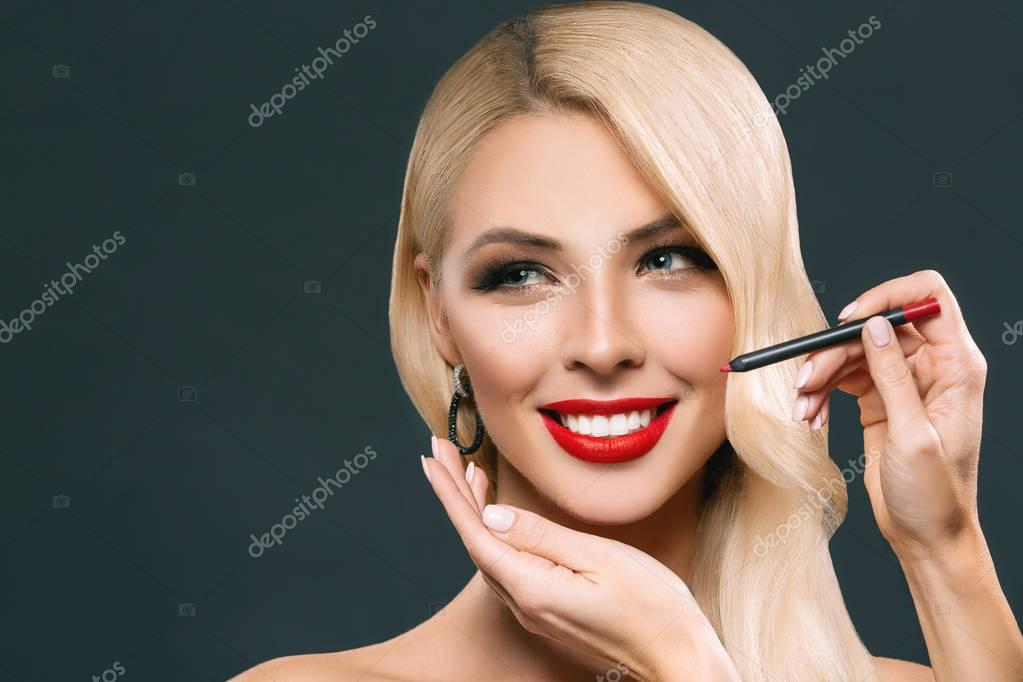 beautiful smiling woman making red lips with cosmetic pencil, isolated on grey
