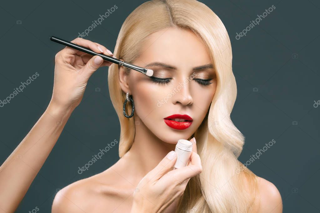 beautiful blonde woman applying glamorous makeup with eyeshadows, isolated on grey