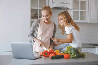 pregnant mother and daughter cooking together and looking at laptop