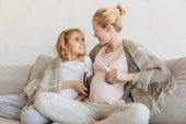 Fotografia madre incinta e figlia dando per ascoltare musica per bambini non ancora nati
