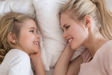 top view of smiling daughter and mother lying on bed and looking at each other