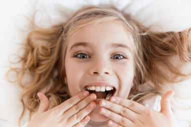 top view of smiling adorable child lying on bed and covering mouth with hands