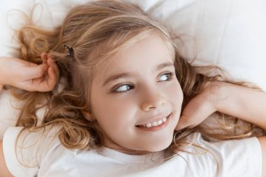 top view of smiling adorable child lying on bed and looking away