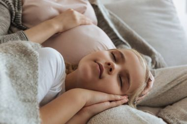 cropped image of daughter sleeping on pregnant mother legs