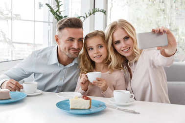 Beautiful young family taking selfie at restaurant stock vector